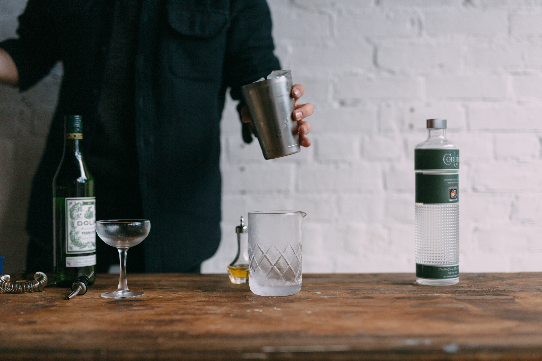 Dolin Dry Vermouth, Martini Glass, Bitters Bottle, Jigger, Corbin Gin, in a shaker