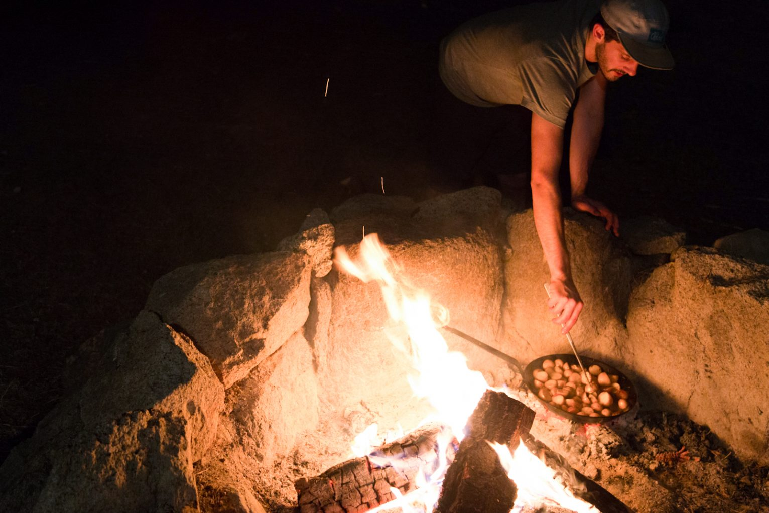 Josh Reeder-Esparza cooking potatoes over the fire