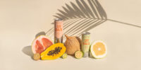 Lei Back CBD Sparkling Water flavors Pomelo and Guava placed next to a tropical fruit display