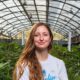 Woman standing proudly in front of her indoor cannabis farm
